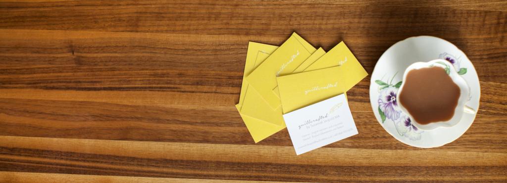 Gelbe Visitenkarten von Susannah Leopold, die neben einer Teetasse liegen.